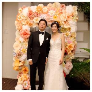 Alex & Claudia infront of the paper flower wedding arch