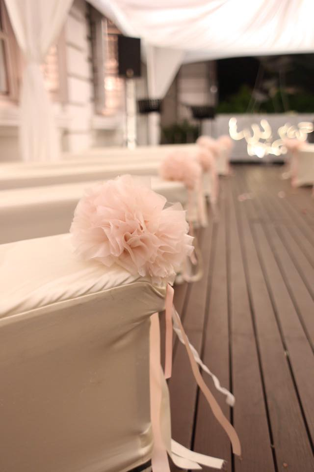 aisle benches with ribbon streamers and organza pom poms
