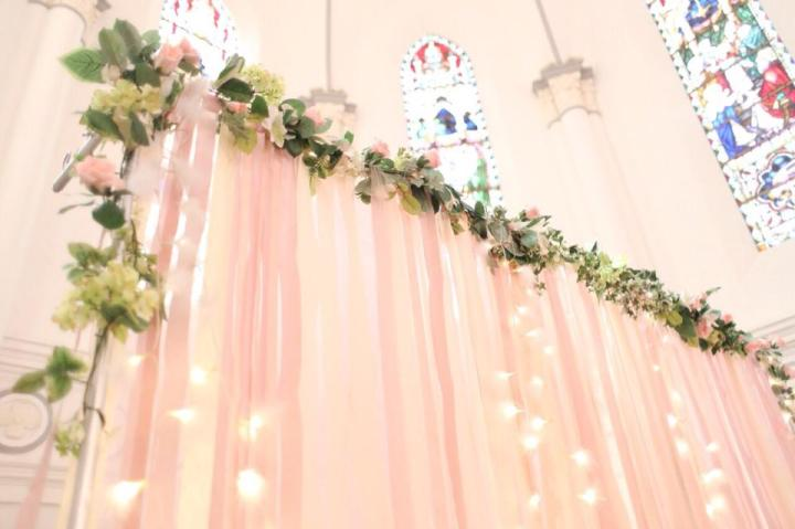 Pastel coloured streamer backdrop with fairy lights and flowers