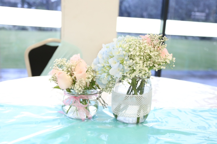 Flower centerpiece in jars (roses, hydrangea and baby's breath)