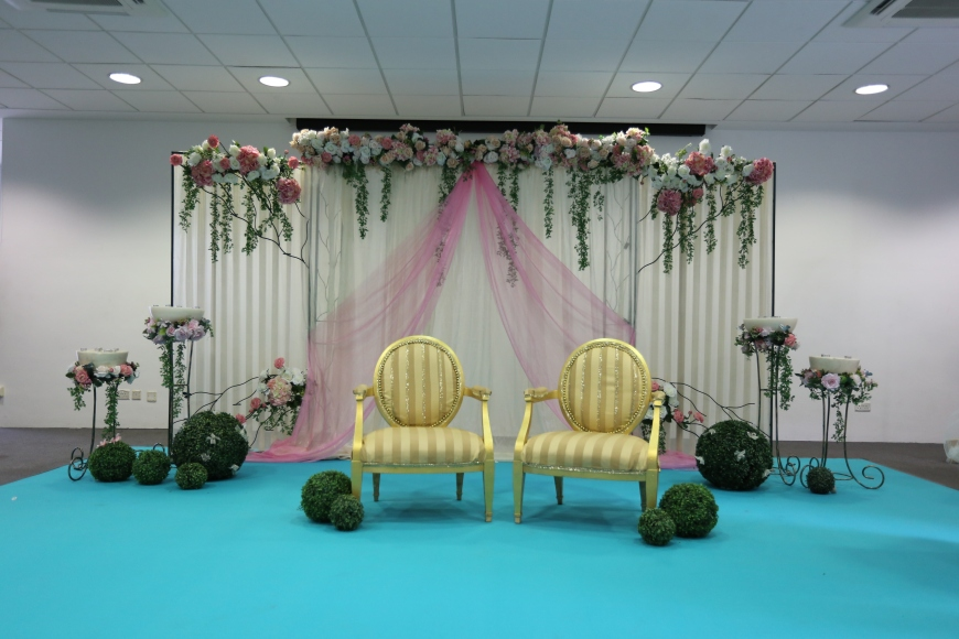 Stage decor with dias, flower stands, garden balls, couple seats and blue carpet