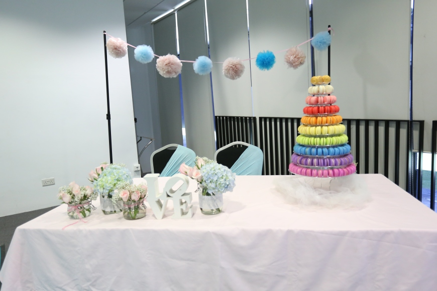 Bridal table with hanging pom poms, flower centerpieces and colourful macaroon tower