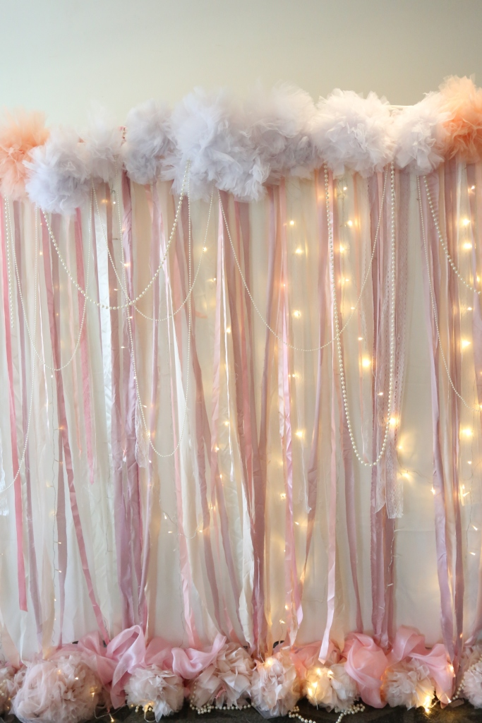 Photobooth backdrop with fairy lights pearls and pom poms
