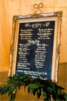 Wedding program written in gold ink on a chalkboard with a gold frame